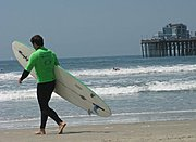 Man Heading out to Surf, Oceanside