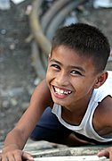 Young, Smiling Filipino Boy Climbing Wall