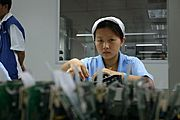 Young Woman Working in Electronics Factory