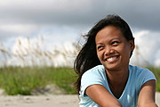 Young Asian Woman Sitting, Smiling on Beach