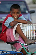 Image of a Smiling Street Boy on a Bicycle in Front of a Red Car with Dirty Feet