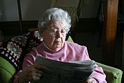 Elderly Woman Reading the Newspaper at Home