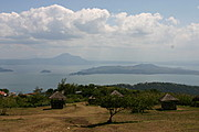 Taal Volcano Seen Through a Rolling Hill with Nipa Huts