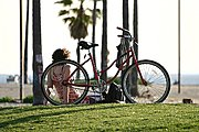 Woman Relaxing Next to Bike, Venice Beach, CA