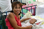 Smiling Grandmother Posing Beside a Sleeping Baby in the Nursery