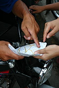 Hands of Tricycle Drivers Pointing to a Map Location in Angeles City, Pampanga