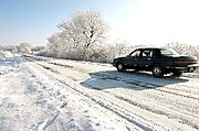 Car Along Rural Road in Wintertime