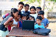 Children Gathered Around a Laptop Computer in the rural Philippines