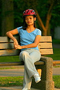 Young Woman with Bike Helmet Sitting on Bench