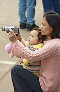 Mother and Child Using Camcorder at a Parade