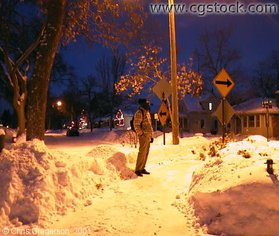 Chris and snowbanks under a streetlight