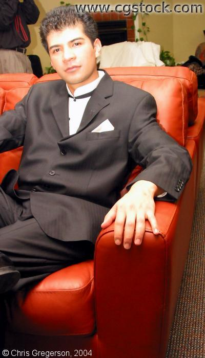 Man in Suit Sitting on Red Sofa