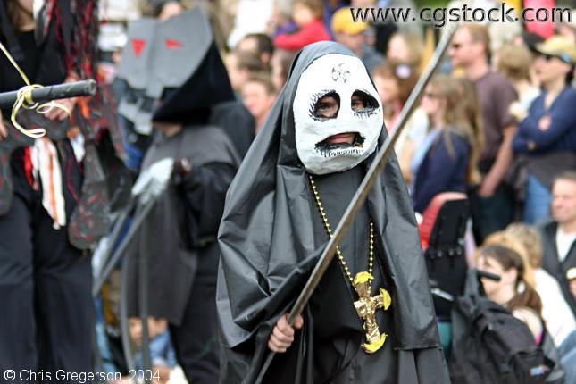 Child in May Day Parade, Wearing Mask and Dressed in Black