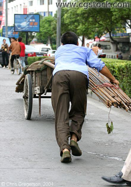 Worker Hauling Metal Rods