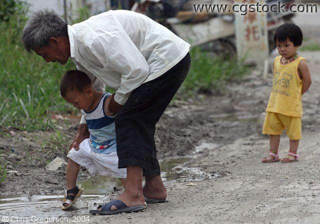 Older Man Helping a Young Boy