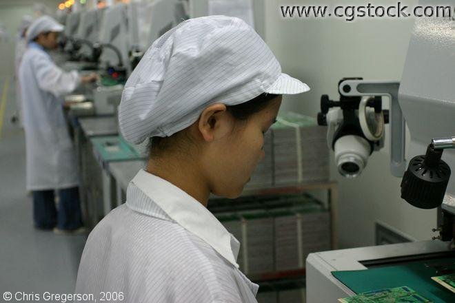 Row of Workers Inspecting Electronics