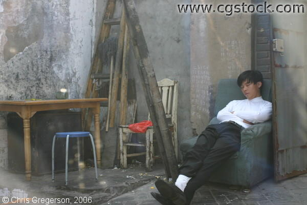 Man Sleeping in a Beijing Hutong in an Armchair