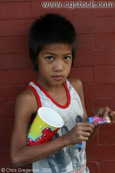 A Young Filipino Boy Eating a Candy Bar.
