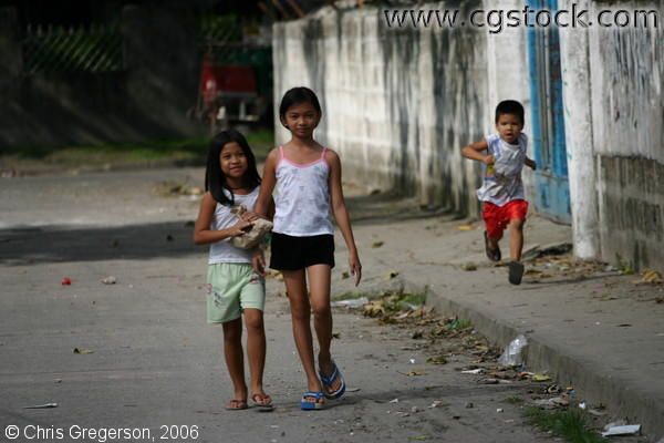 Picture of Two Children Walking and Another Running on a Street, Angeles City