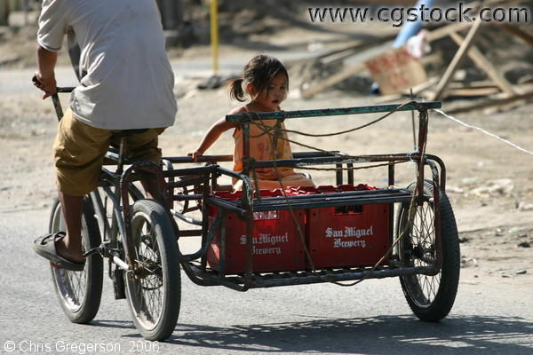 Toddler Being Carried on a Moving Tricycle Along With Two Red San Miguel Beer Cases
