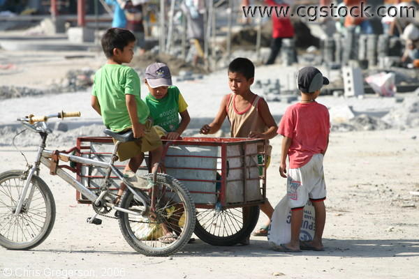 Four Boys Around a Tricycle Gathering Bric-a-brac from a Construction Site