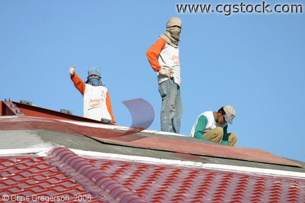 Three Men Laying the Brick Roofing of a Building, One Doing a Thumbs Up Gesture