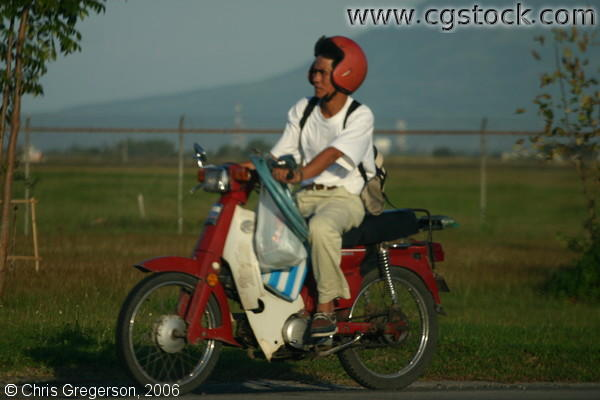 Man Riding a Parked Motorcycle with Red Helmet