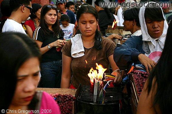A Brown-Skinned Lady Lights Colorful Candles in the Middle of a Crowd