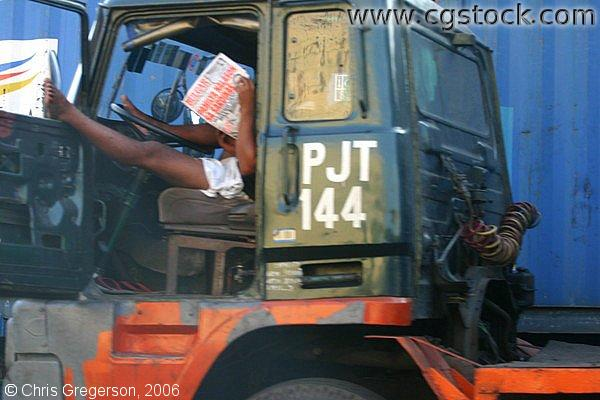 Filipino Truck Driver Reading a Newspaper in his Cab