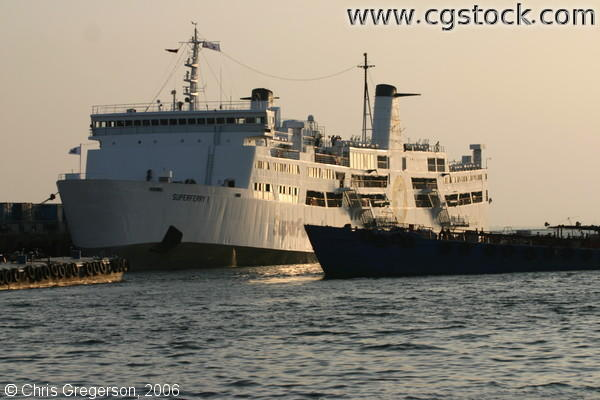 Boat Transfers Goods to Superferry 1 Passenger Ship