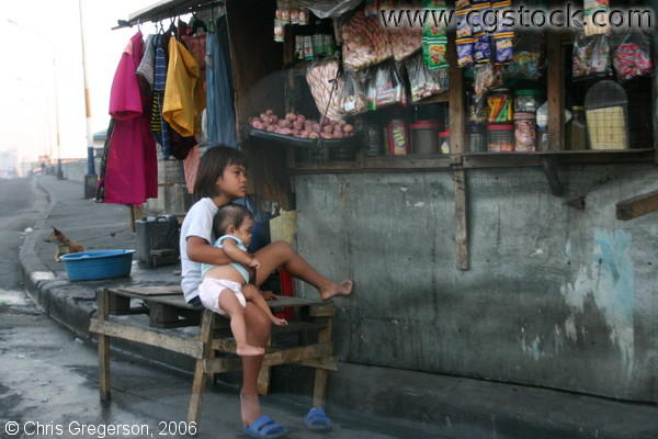 Sari-Sari Store in Tondo and a Filipina Girl Carrying an Infant