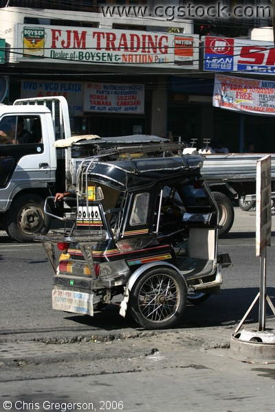 A Parked Tricycle Near Some Business Establishments