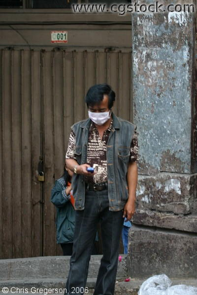 A Man Texting Wears a Face Mask Due to Meningococcemia Epidemic in Baguio City, Philippines