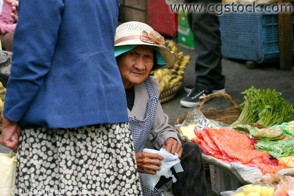 An Old Woman Selling Vegetables Peeks Through a Passerby in Baguio Public Market
