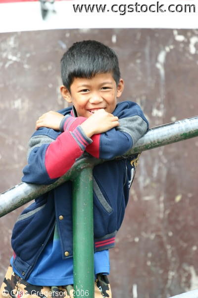 Smiling Boy Leans Over the Railing of a Sidewalk in Baguio City, Philippines