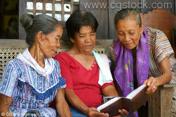 Three Filipina Women Looking at Photos