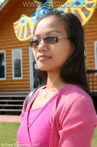 Asian Woman with Sunglasses by Roadside Attraction